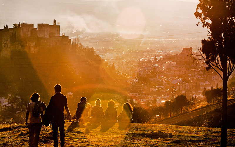 Group of people sat on a hill at sunset