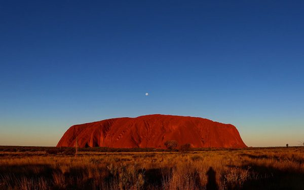 Sunset over Ayres Rock with the moon above it