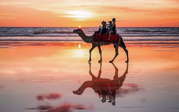 Three people riding on a camel on the beach in Broome