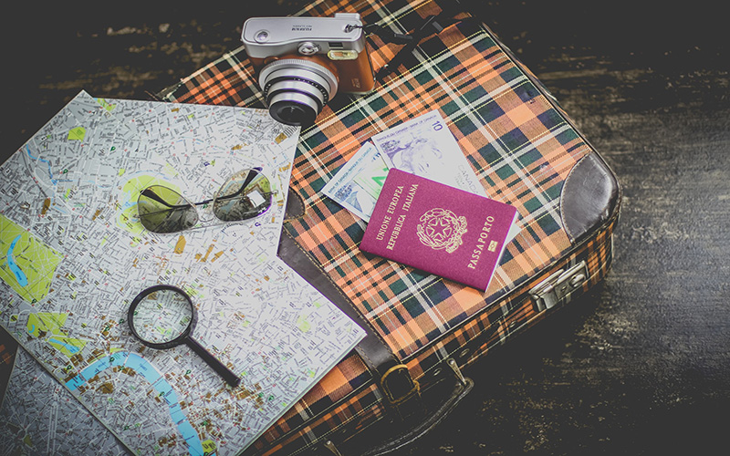 Travel essentials on top of a suitcase